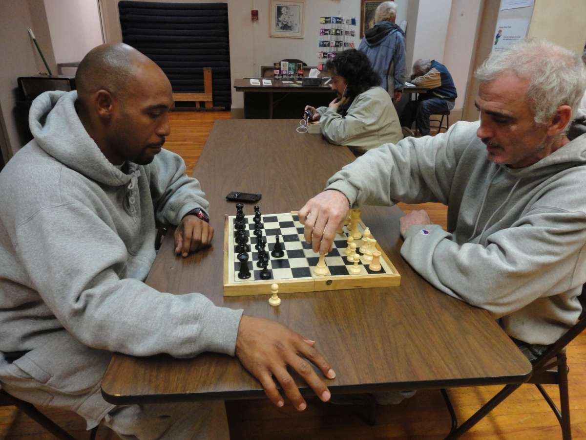 Two men play chess in the recreation center