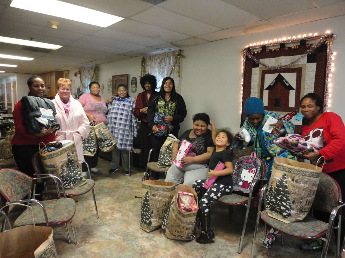 Women receiving Christmas gifts at the Karis Home